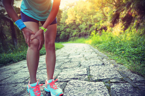 Athlete holding her knee for natural pain management