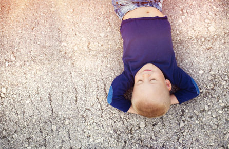 Child lying on rocky land relaxing