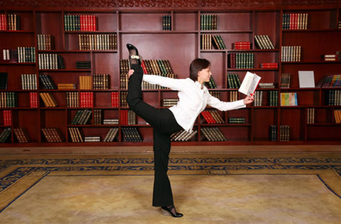 Woman reading book while practicing yoga
