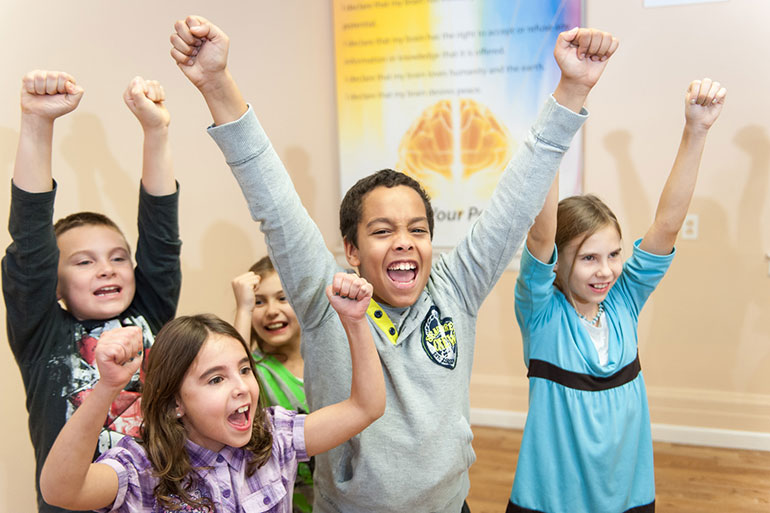 Brain power classroom with children raising arms and voice