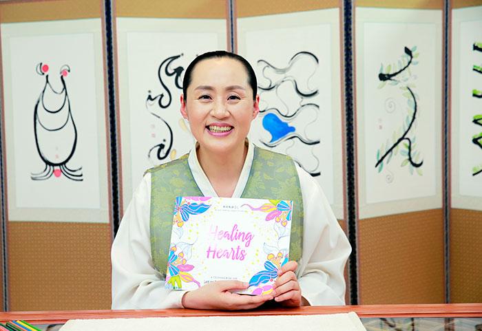 Manwol, creator of healing hearts displaying her books