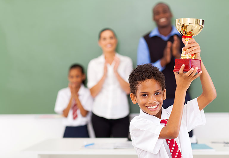 Boy holding a cup after winning a contest