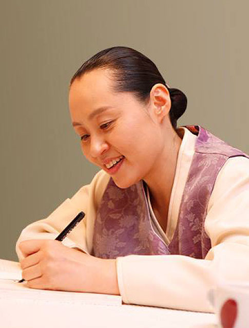 Manwol Son writing on a paper with smile on her face