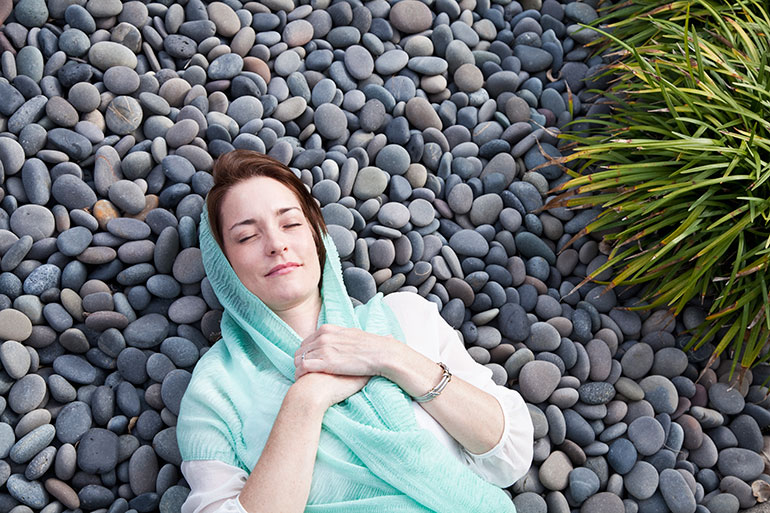 Woman lying on pebbles doing some relaxation