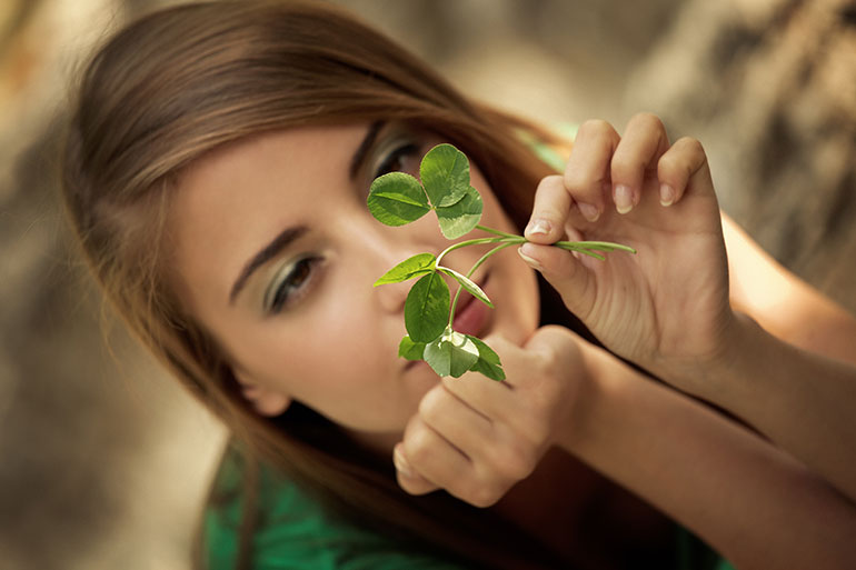 Woman holding stem of leaf while lying