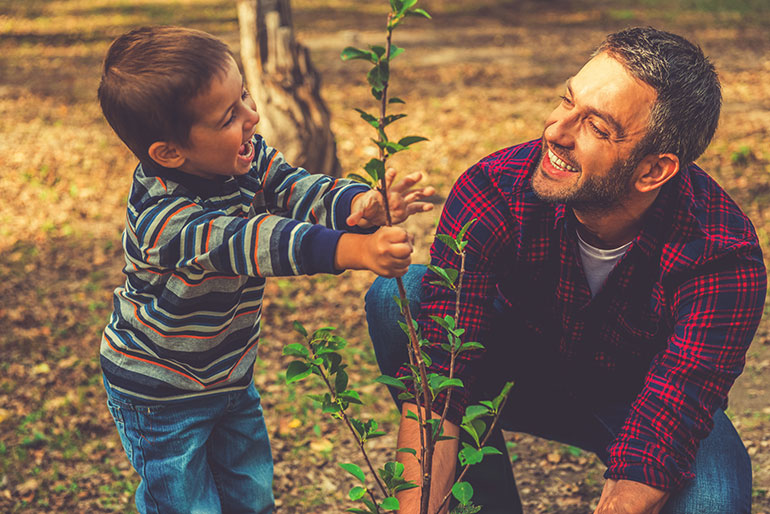 Boy and man planting a tree with some smiling moments
