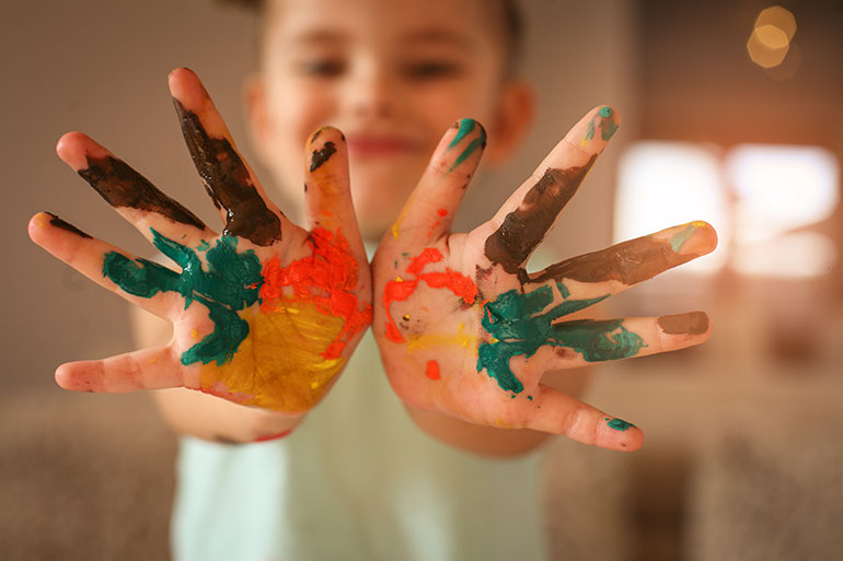 Boy showing hands with splash of colors