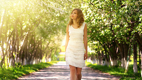 Woman walking on pathway with trees on both sides