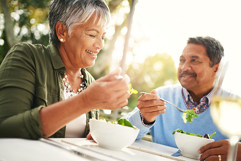 Man and woman eating salad with little smile